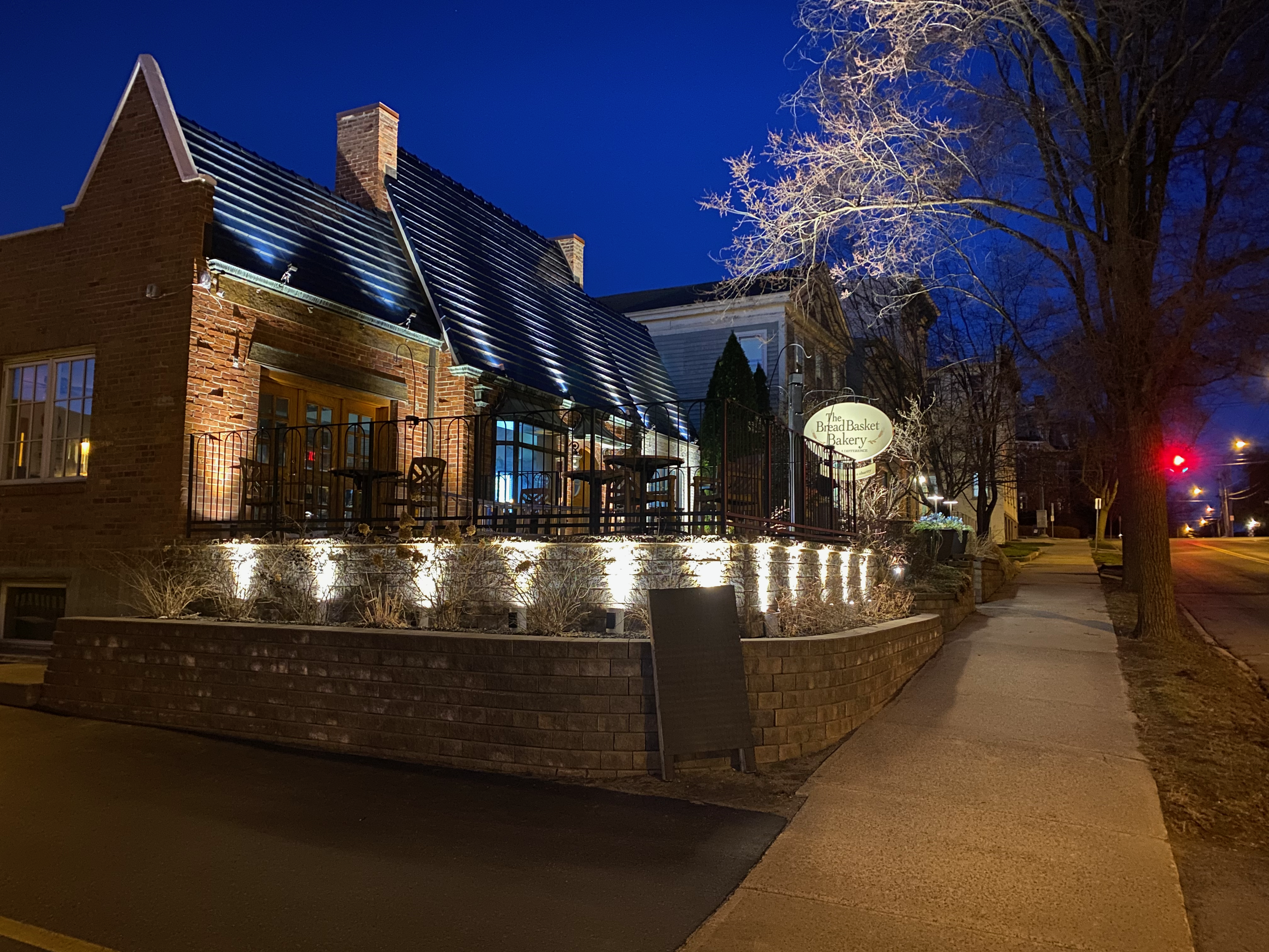 Local bakery with landscape lighting lighting up a rock wall and roof