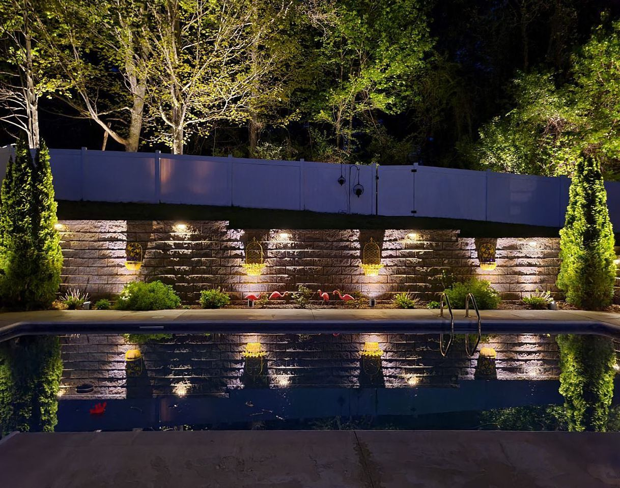 a pool with landscape outdoor lighting