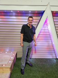 Aaron standing in front of a home with color changing soffit lights for landscape down lights